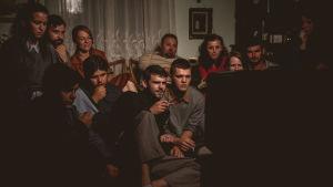 Ihmiset ovat kokoontuneet katsomaan elokuvaa pienestä televisiosta dokumentissa Chuck Norris vs kommunismi
