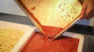 Köttfärssås och pasta i stora behållare