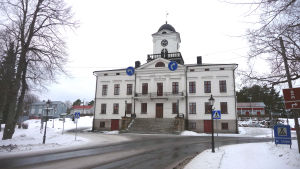 En byggnad med vit fasad och ett klocktorn på taket.