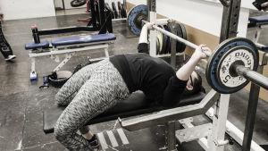 """En kvinna ligger på en bänk. Hon svankar väldigt mycket och håller i en skivstång med vikter på. Hon """"bänkpressar""""."""