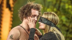 Maren doftar på en mans hals med förbundna ögon.