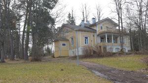 Ett gult hus med vita knutar på en kulle. Det heter Villa Grantorp.