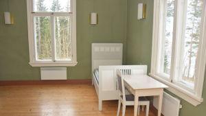 Ett rum med gröna tapeter och vita möbler i Villa Grantorp.