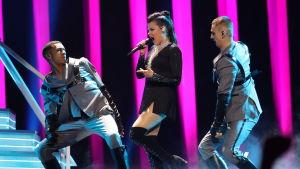 kvinna som sjunger med två manliga dansare