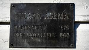 """Kyltti seinässä, jossa lukee """"Pulsan asema, rakennettu 1870, peruskorjattu 1997"""""""