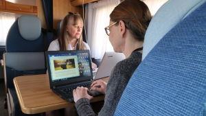 Sirpa Madsen och Sanna Jokinen arbetar vid sina datorer i husbilen.