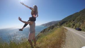 En kvinna sitter på en mans axlar. De står vid sidan av en väg och blickar ut över havet. Båda två vinkar med ena handen.