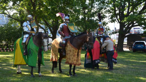 Tre  riddare till häst på ett tornerspel.