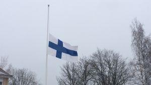 Finlands flagga på halvstång.