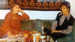 två kvinnor samtalar i en soffa