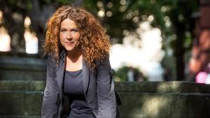 Programledare Anna Lindman framför stenmur.