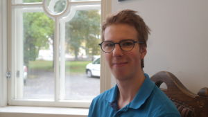 Teologiestuderande Alexander Nykvist sitter vid ett fönster