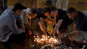 Männsikor tänder ljus i Charlottesville efter dödsfall under högerextrem demonstration.
