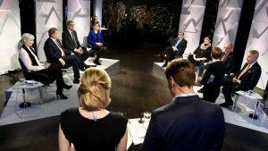 Presidentkandidaterna sitter i studion. Debattledarna har ryggen mot kameran.