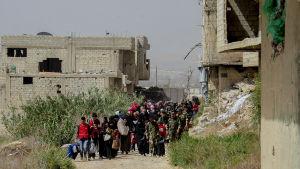 De första civila som evakuerades från Douma eskorterades av syriska hjälparbetare och soldater