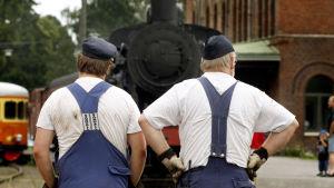 Två män i blåställ står med ryggen vänd mot kameran och tittar på ett gammalt lok.