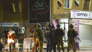 Säkerhetsstyrkor står utanför den turkiska restaurangen i Ouagadougou i Burkina Faso, som blev attackerad av beväpnade män.