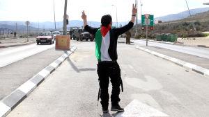 En palestinier demonstrerar mot judiska bosättningar på Västbanken.