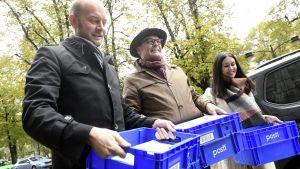 Sampo Terho, Matti Torvinen och Tiina Elovaara håller plastlådor med Blå framtids anhängarkort.