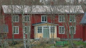 Stort österbottniskt trähus i skogsglänta.