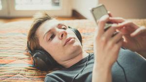 En kvinna med kort hår ligger på en säng och lyssnar på musik. Hon har hörlurar på sig och tittar på sin smarttelefon.