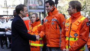 Franrikes president Emmanuel Macron skakar hand med räddningspersonal under minnesceremonierna för Bataclanattacken.