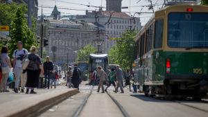 Raitiovaunukiskot ja raitiovaunuja jalankulkijoiden joukossa Helsingissä kesällä.