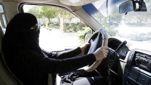 En beslöjad saudisk kvinna sitter bakom ratten i Riyadh i oktober 2013.