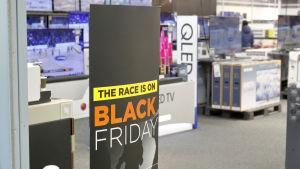 """En skylt där det står """"The race is on, Black Friday"""" i en elektronikbutik"""