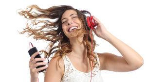 En kvinna med långt lockigt hår lyssnar på musik i hörlurar, från sin smarttelefon. Hon ser väldigt glad ut. Hon ler och dansar.