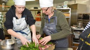 Ieva Židonytė och Magdalena Ek håller på att laga korv.
