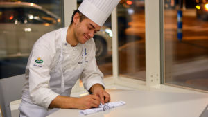 Kocken Samuel Mikander sitter vid ett bord och skriver en autograf på en liten tröja.