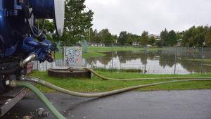 Tankbil pumpar bort vatten från idrottsplanen i Karis.