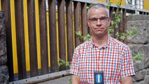 Äldre poliskonstapel Niklas Kråknäs i somrig skjorta, med polisbricka runt halsen.