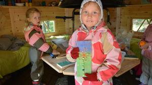 Två barn pysslar inne i en kåta.