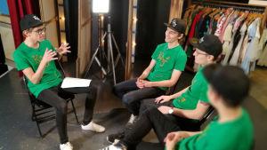 Christoffer Strandberg sitter mitt emot Kevin Holmström, Axel Åhman och Jakob Norrgård. Alla är iklädda gröna t-skjortor och svarta kepsar. Christoffer håller på att ställa en fråga. De sitter på en scen och i bakgrunden syns rekvisita och kläder.