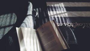 En person klädd i yllestrumpor läser bok.
