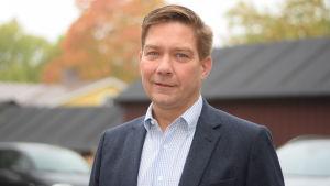 En man i blå kostym som är riksdagsledamoten Thomas Blomqvist.