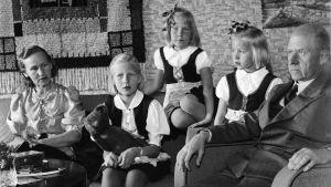 Bister far i stol ,med barn och fru  i soffan