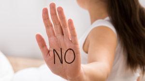 """En kvinna med ansiktet bortvänt som har text """"No"""" skriven i handflatan som hon vänder mot kameran."""