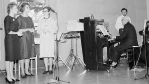 En man spelar på piano och tre kvinnor sjunger.