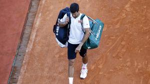 Djokovic går på en grusplan med kassar.