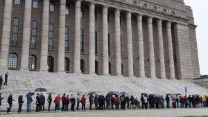 Många köade i duggregnet till riksdagshuset.