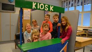 Glada elever bakom i en leksakskiosk.