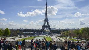 Eiffeltornet i Paris med turister i förgrunden.