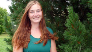 profilbild på Jennifer Molnár-Koschinsk1. Bakom en förädlad tall
