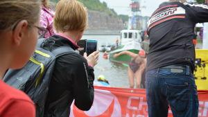 Unga triathleter kommer upp från ån.
