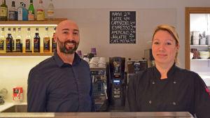 Nico Chavo och Kaija Heiliö poserar bakom disken i kaféet de jobbar i.