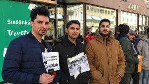 Tre män från Irak demonstrerar på gågatan i Åbo.
