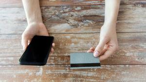 Händer som håller i en smarttelefon och ett bankkort.